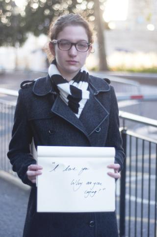 """""""Te quiero, ¿por qué lloras?"""", dice el cartel de esta superviviente de una violación. Es parte del proyecto Unbreakable, de Grace Brown."""